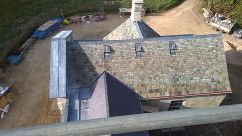Westmorland slates, conservation roof-lights, lead roll-top ridge, lead-work to valley and pediment.