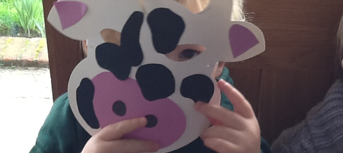 child wearing a cow mask