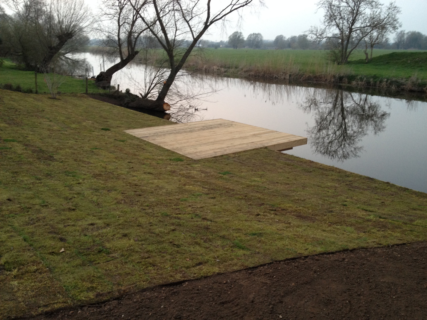 Large cantilevered deck and jetty built beside a river in Cambridgeshire.