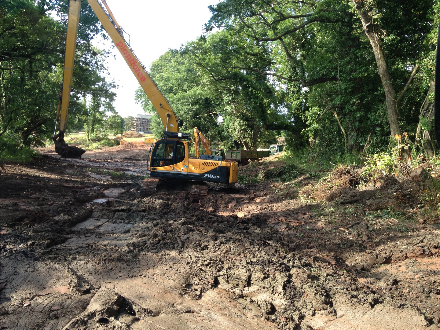 Excavator in large lake removing silt at Sand hill park Bishops Lydeard