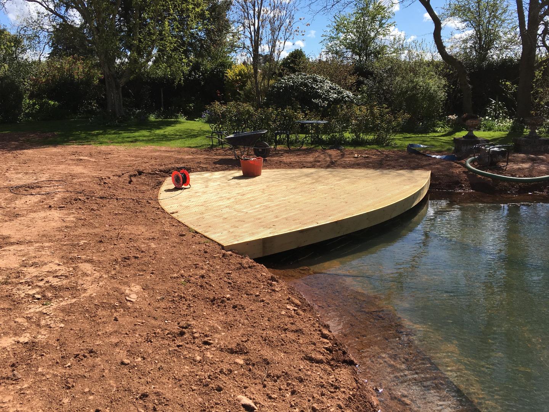 Sun lounger deck built beside a pond in Somerset
