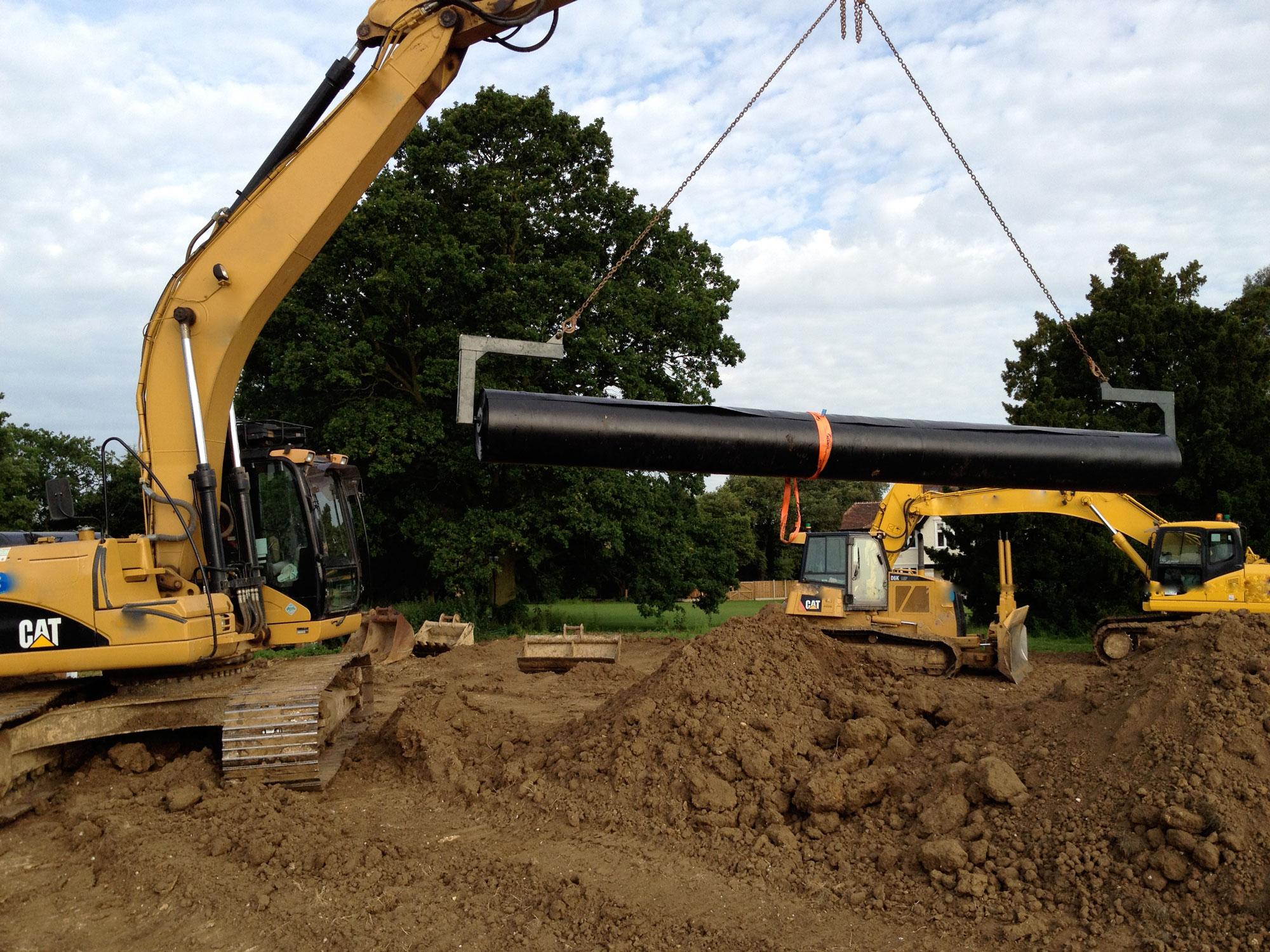 Excavator handling a roll of liner