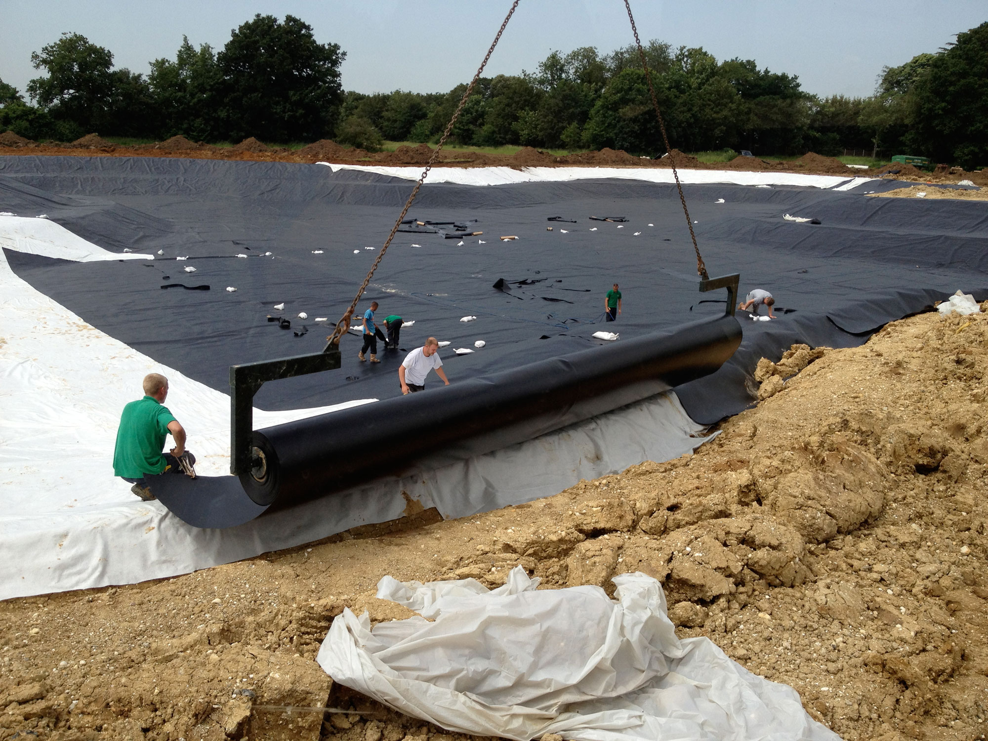 A roll of HDPE liner being lowered into position for a lake construction