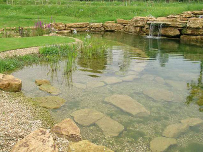 Swimming pond with liner and rock feature