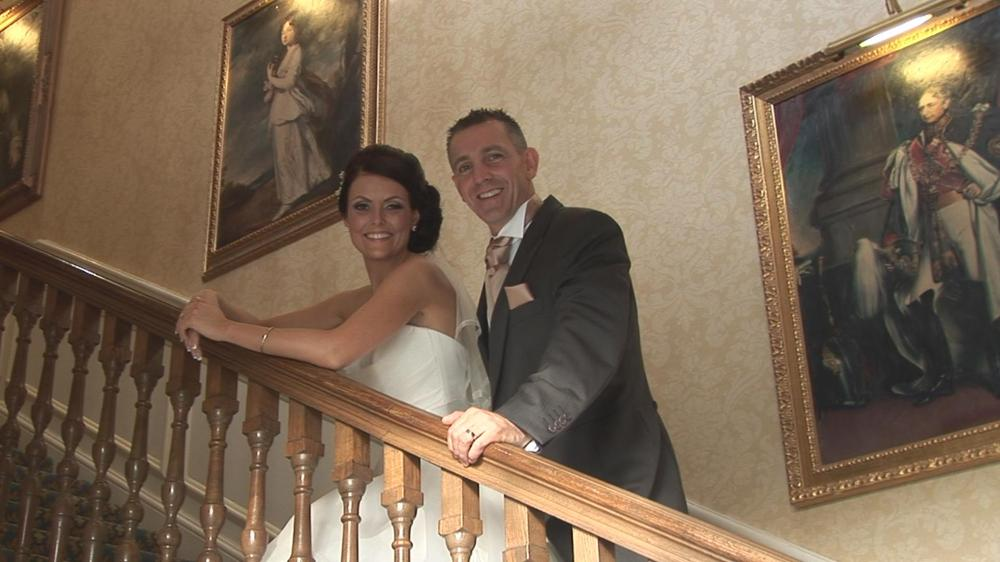 Just married couple stood on stairs together.
