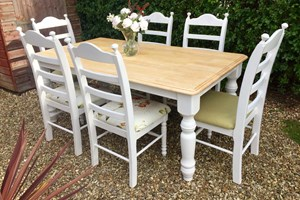 Country farmhouse dining table and chairs, painted and distressed with natural pine top and two-toned upholstery.