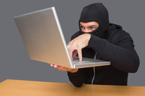 Criminal committing cyber crime on laptop