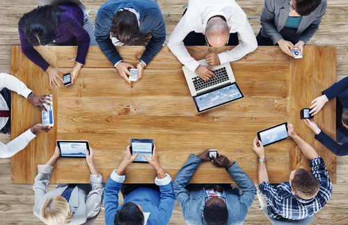 Office workers around a table using digital devices