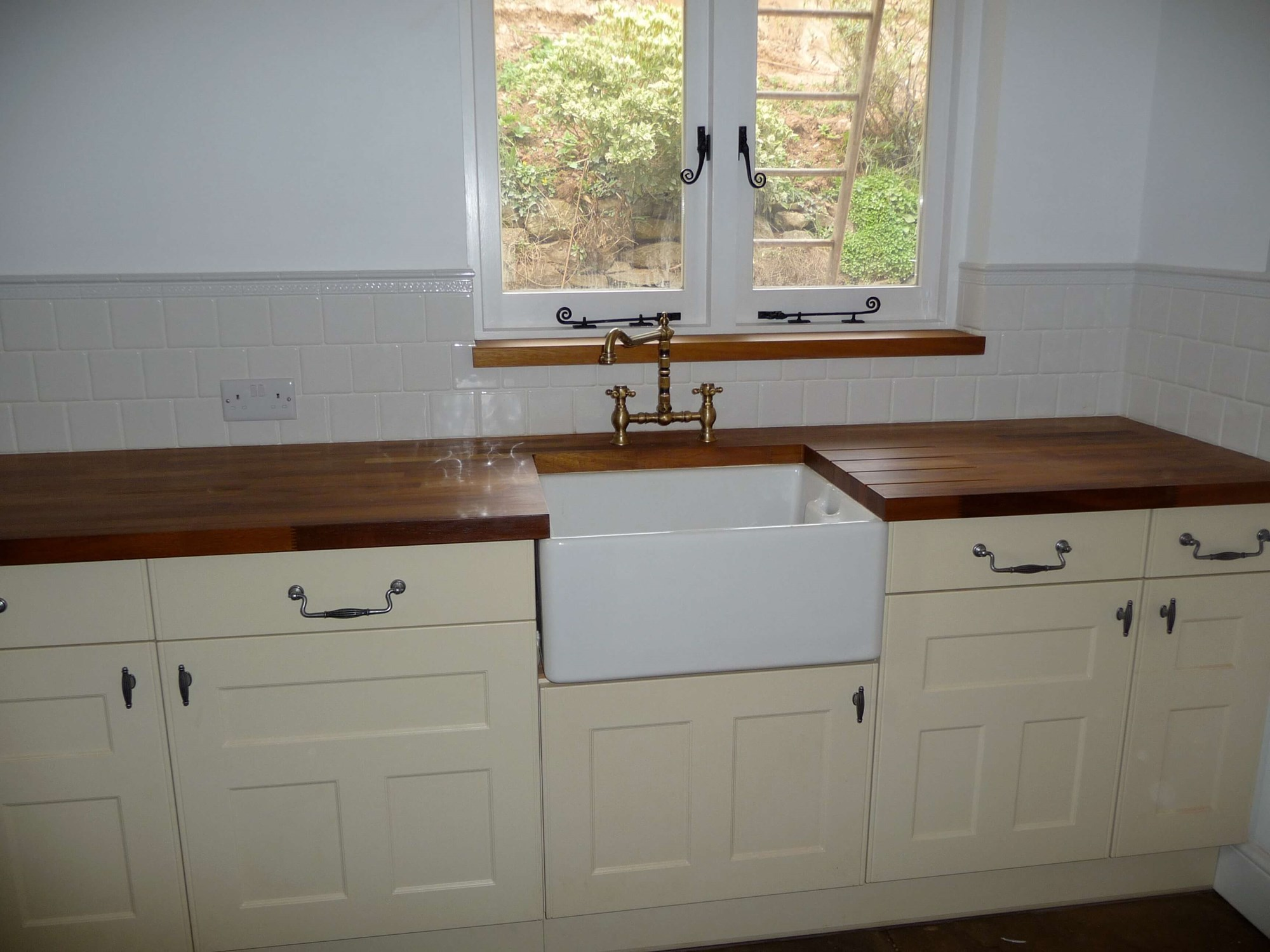 Farmhouse-style utility room. Hardwood worktops and floor is recycled stone.