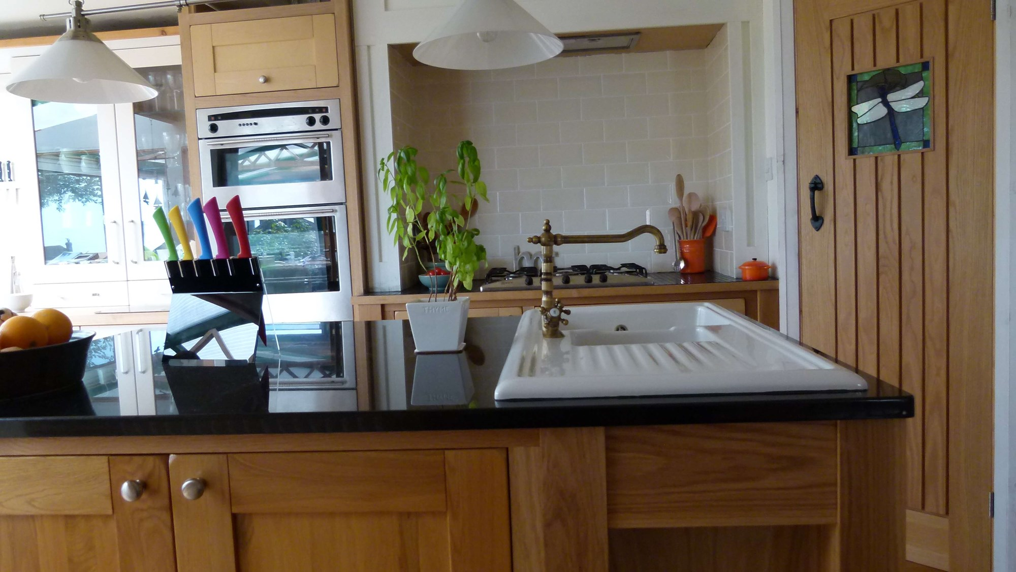 Kitchen with central island crafted from American white oak, topped with black granite. One and a half bowl china sink with traditional French mixer tap