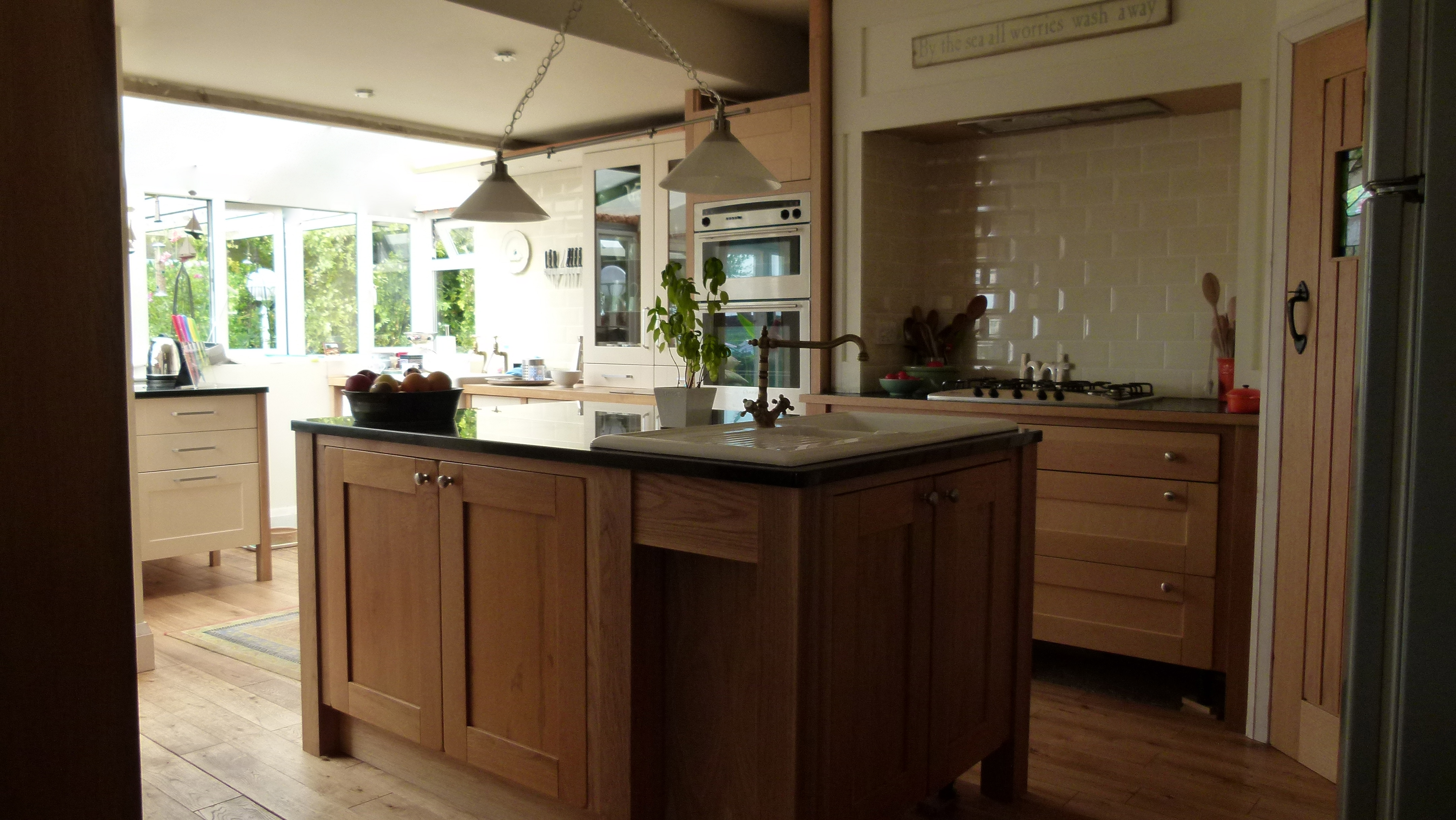 Kitchen with solid white oak counter tops, with a butlers sink fitted creating independent work areas.