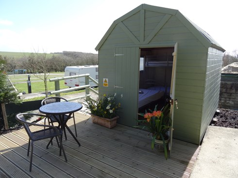 The Beach Hut sleeps 3 set in an elevated sunny corner, with outside BBQ and picnic table