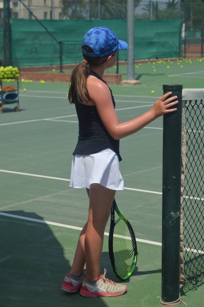 Female Junior Tennis Player | Resting at Tennis Net