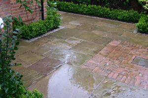 reclaimed york stone paving slabs and reclaimed bricks in the rain