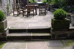 A delightful dining courtyard laid with reclaimed york stone paving using reclaimed york stone kerbs as steps to the different levels.