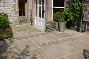 Reclaimed yorkstone paving laid random look warm and mellow in this old courtyard