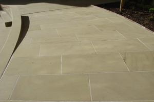 Newly sawn coursed yorkstone paving.