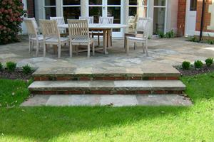 Reclaimed York stone paving has been used here to create a patio and steps leading to the lawn bringing house and garden together.