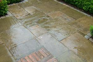 Detail of a reclaimed york stone path with reclaimed brick insets