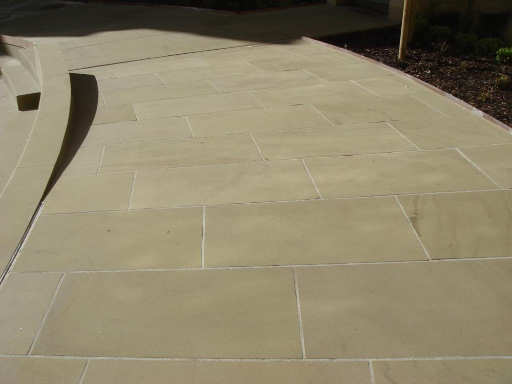 Newly sawn yorkstone coursed paving.