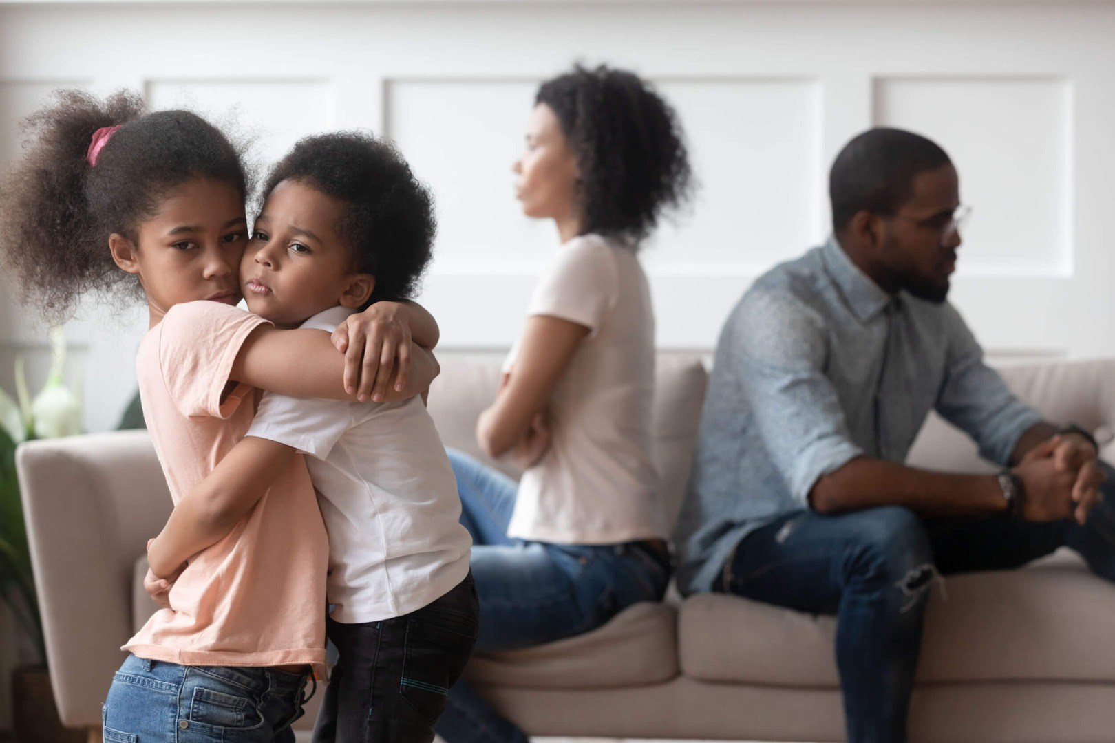 children hugging and parents arguing