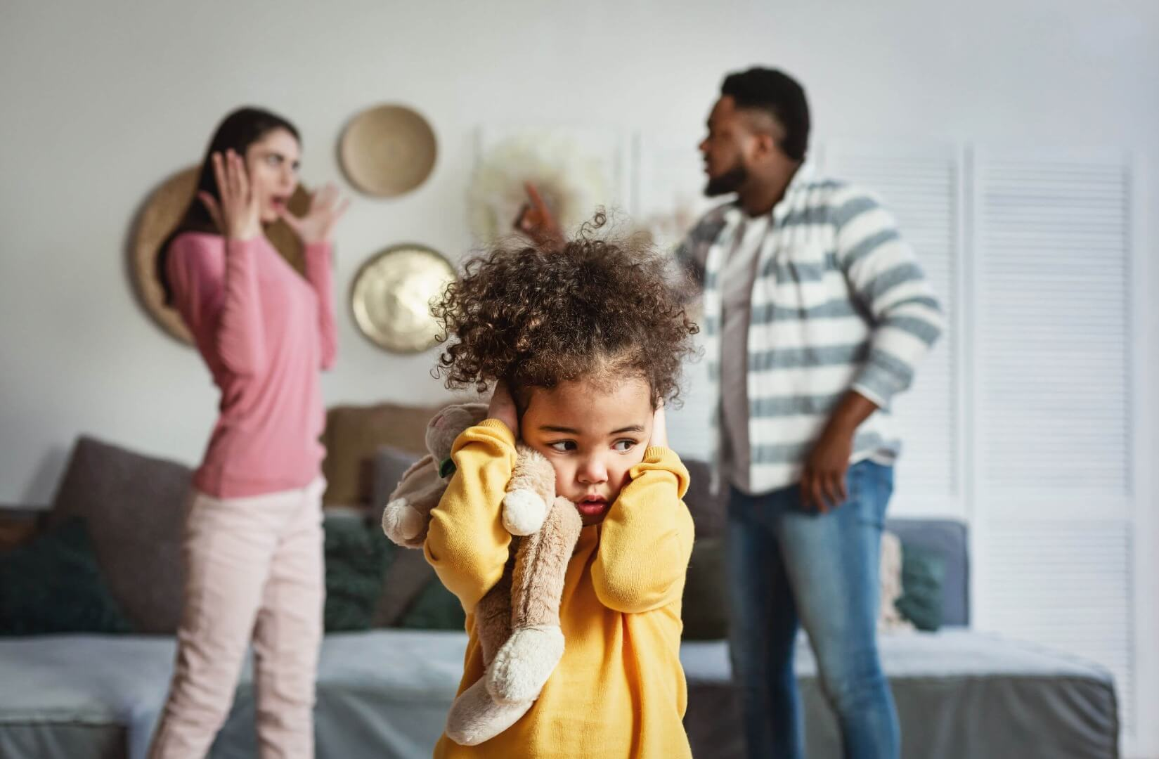 girl with hands over ears and parents arguing