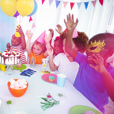Children at birthday party sat on table with deserts
