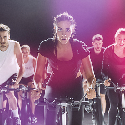 people exercising on bikes in Les mills exercise class