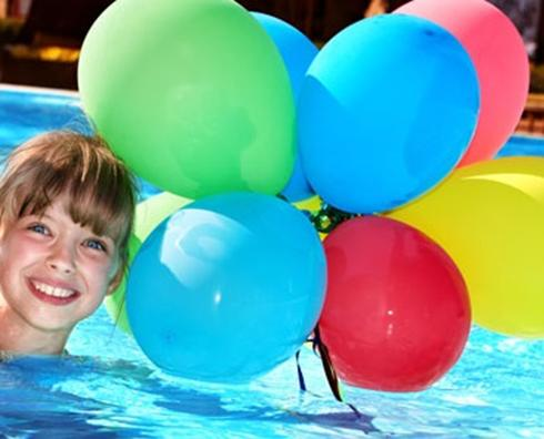 Young girl playing with balloons at a pool party