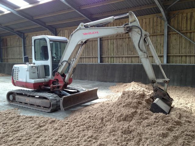 Indoor riding arena sand surface being levelled in somerset