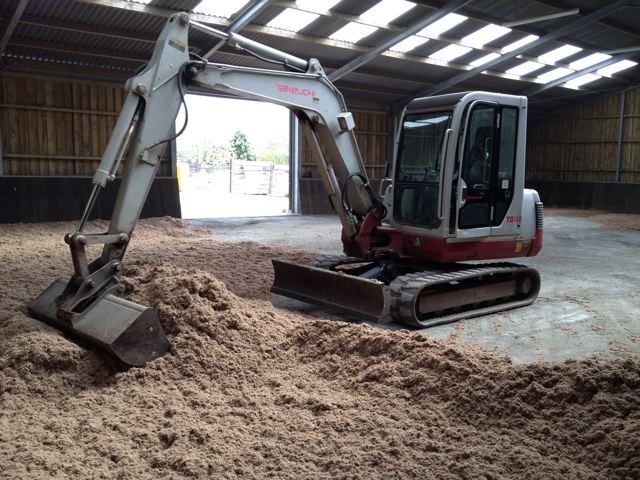 Sand and fibres being levelled inside indoor riding arena