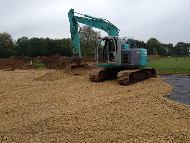 Excavator levelling stone base for riding arena in Cambridge