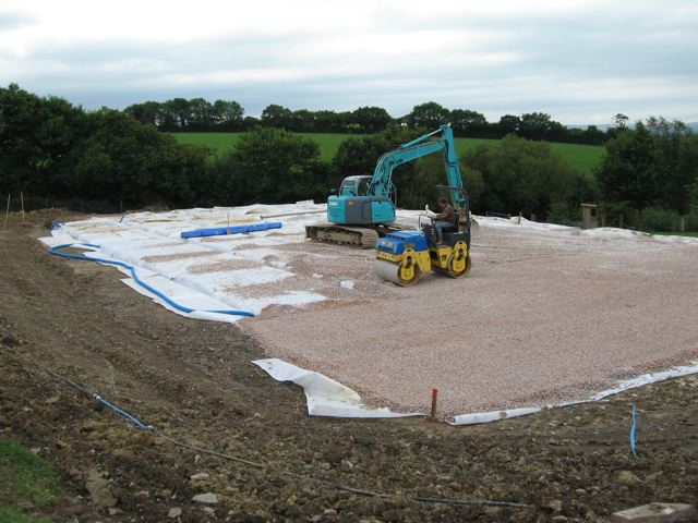 Machines installing stone and drainage on a riding arena in Devon