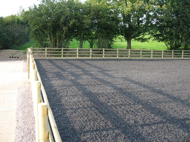 Round post fencing around a rubber chipping surface riding arena
