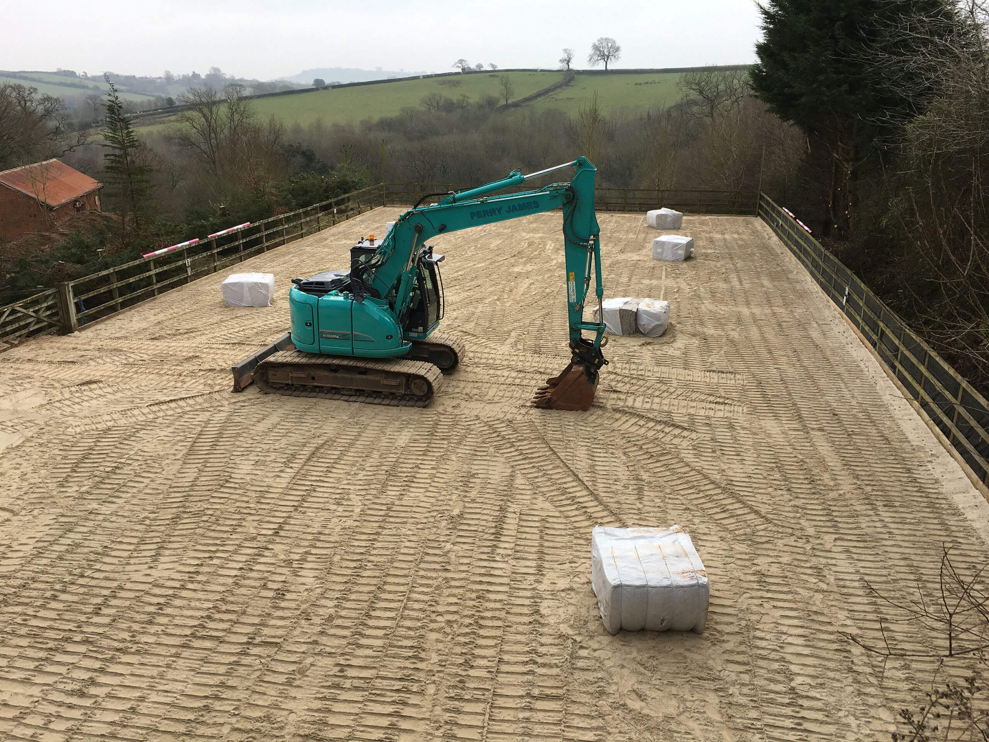 Machine levelling out sand surface ready for fibre installation on a riding arena in devon