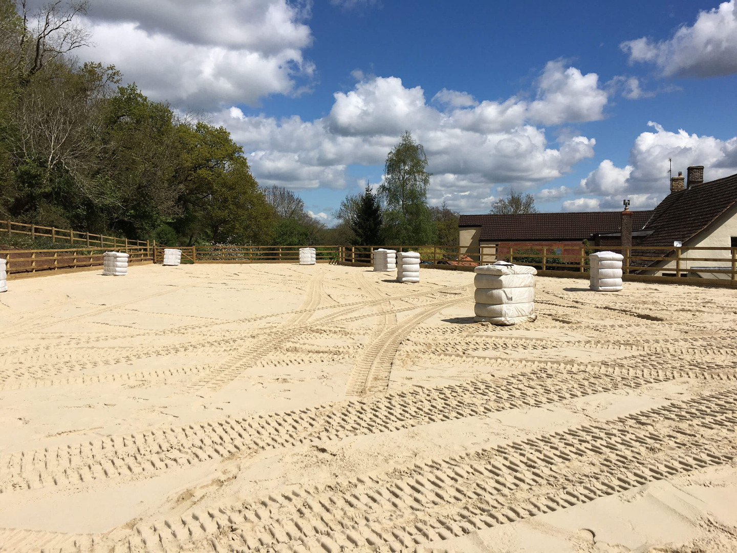 Sand surface installed on a riding arena in Devon with fibres in bales