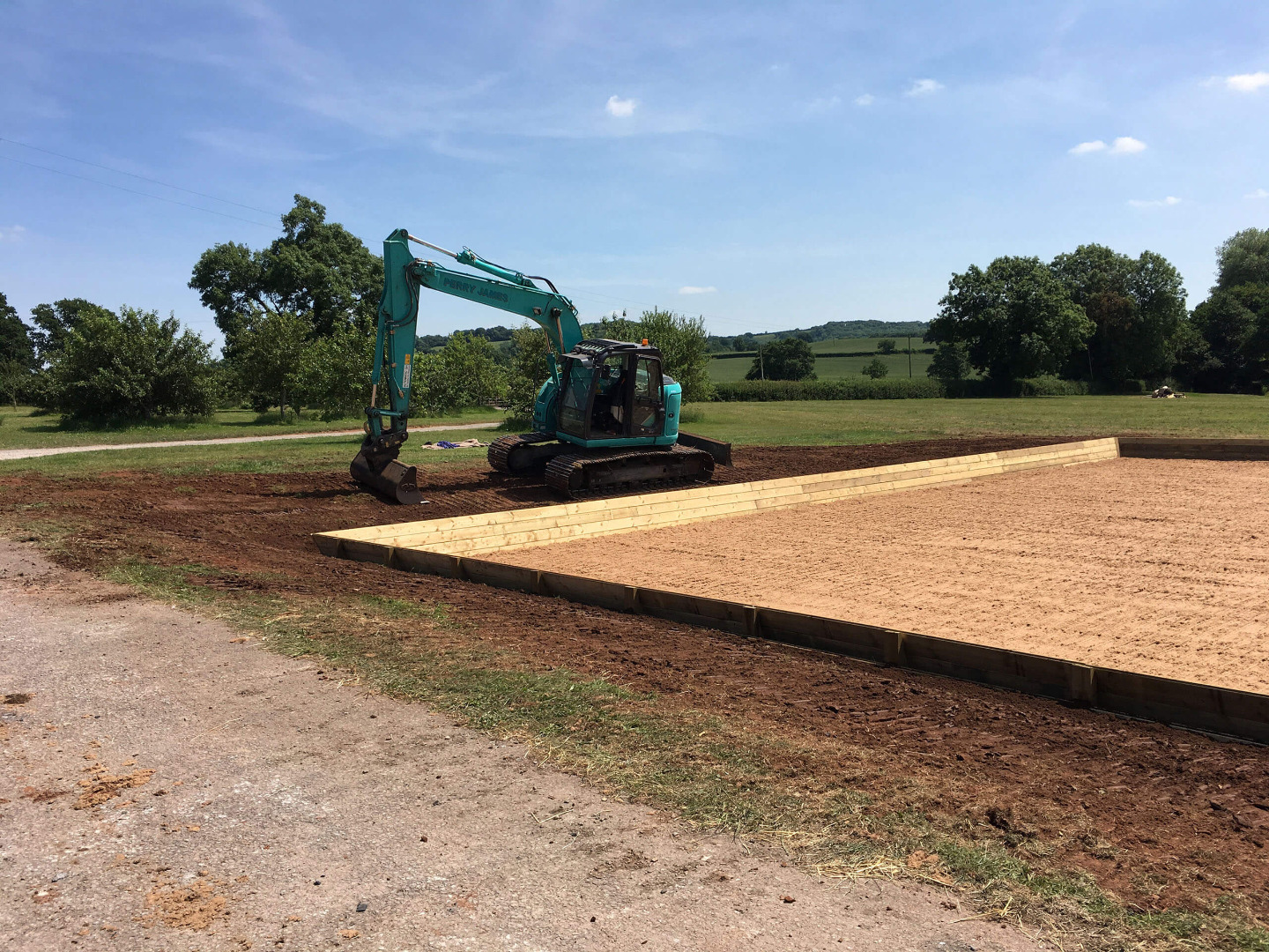 Machine topsoiling around a dressage arena with a waxed fibre surface in somerset