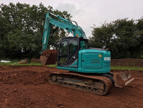 Excavator earthmoving soils for cut and fill excavation on a riding arena project