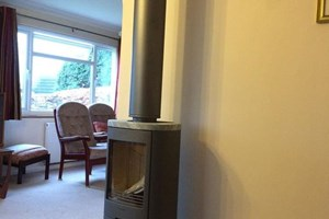 A twin wall flue installation of a Contura stove on a D shaped hearth in the Alresford area.