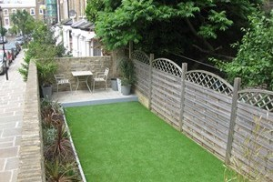 Artificial grass installation with new paving area, timber edging used to create new plant border area.
