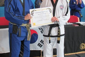Master Beck receiving his 6th Degree Certificate from Senior Master Willie Lim.