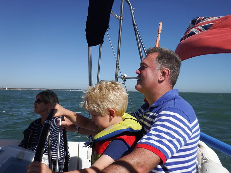 Son and dad at helm