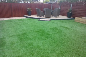 Garden landscaping in Ellesmere Port, porcelain paving, artificial grass, railway sleepers for planting.