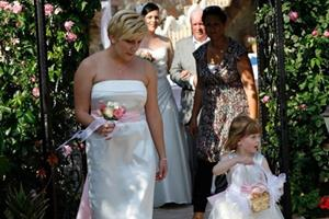 Summer wedding: Adult bridesmaid, ivory strapless gown with flower girl in complementary dress.