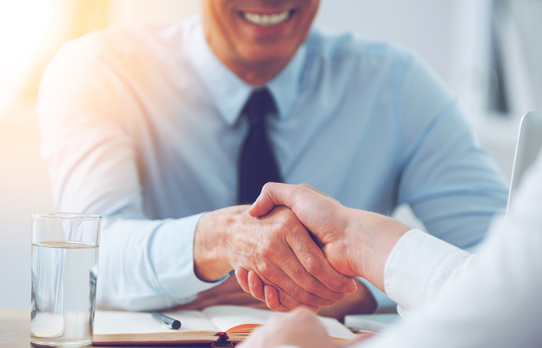 Man in shirt and tie shaking the hand of virtual assistant, Kerry Lummus
