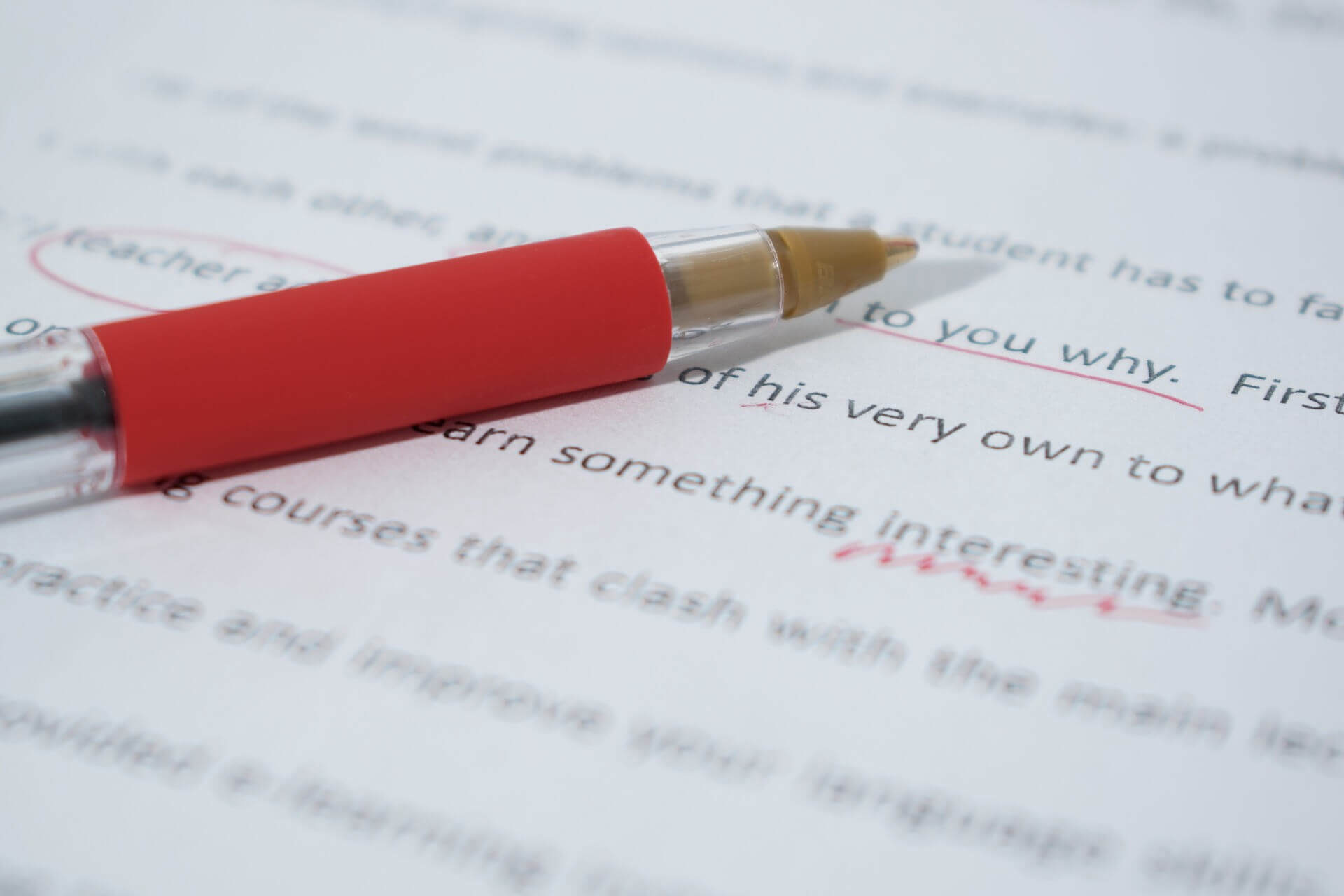 Pen and paper showing corrections being made to a document following proofreading