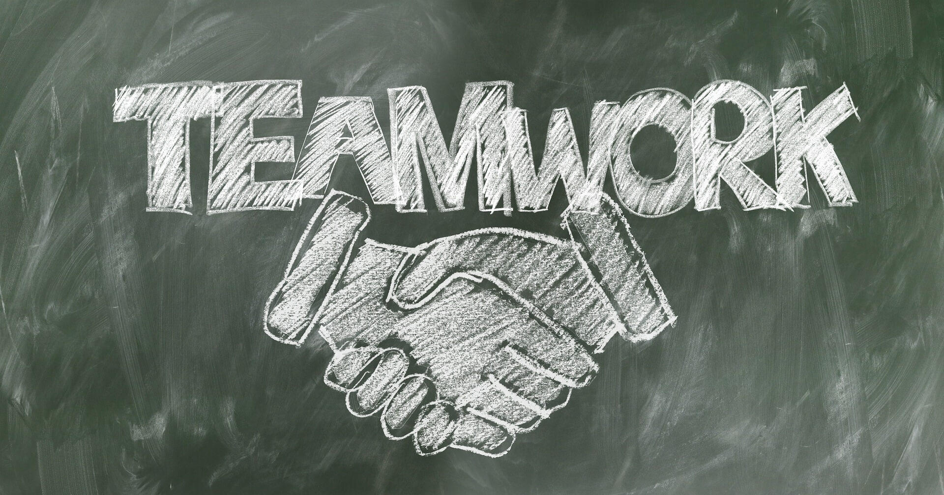 Chalked word 'teamwork' on a blackboard and a picture of a handshake.