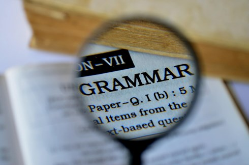 A magnifying glass highlighting the word grammar in a book.