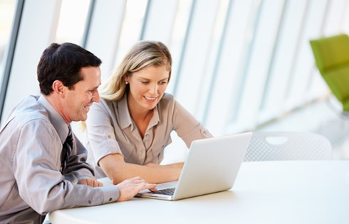 Virtual assistant and potential client studying figures on a laptop with window in background.