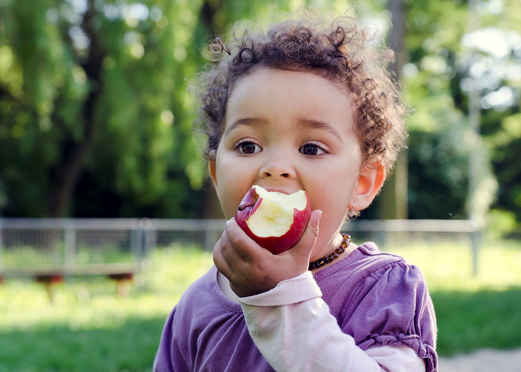 girl sat outside eating apple
